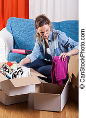 Woman packing stuff - Young woman packing stuff during...