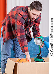 Man packing lamp into a box, vertical