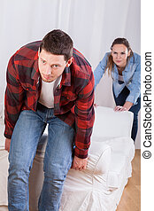 Couple moving the couch - Young couple moving the couch in...