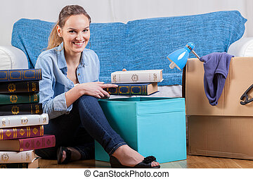 Smiling woman packing books during moving house