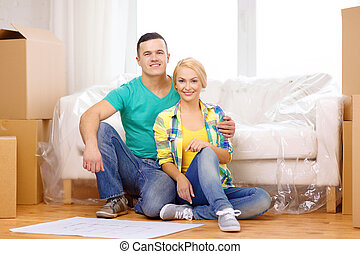 smiling couple looking at bluepring in new home - moving,...