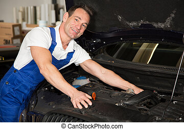 Mechanic in garage repairing car