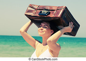 woman with suitcase on the beach Photo in old image style