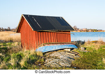 Red boathouse - Old red boathouse by the sea. Boat in front...
