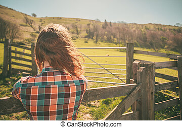 Young woman by a fence on a ranch - Young woman is standing...