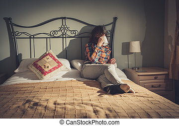 Young woman drinking tea in bed