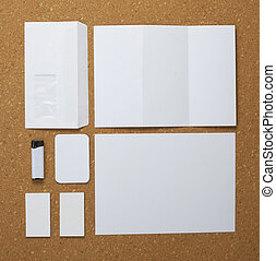 White collection of stationery on corkboard background. -...