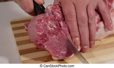Male hands cutting raw pork meat
