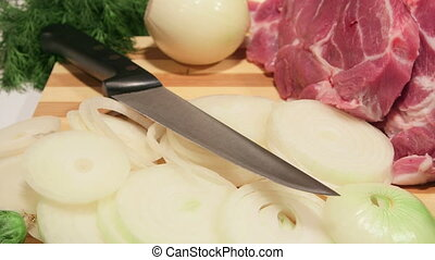Dolly: Sliced fresh pork meat and vegetables on wooden cutting board
