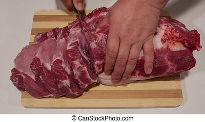 Male hands cutting fresh pork meat on wooden cutting board