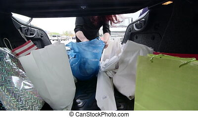 Woman unloads groceries in plastic and paper bags into the trunk of her car