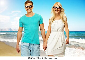 Beautiful smiling young couple walking on a beach