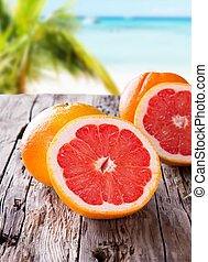 Fresh fruits - Fresh grapefruits and slices on a wooden...