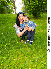 Laughing mother and toddler boy in grass