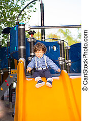 Toddler boy on slide - Toddler boy ready to slideing in a...