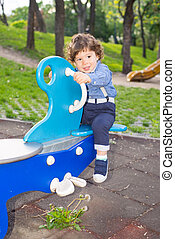 Boy in seesaw looking away - Toddler boy in seesaw looking...