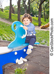 Curly boy on seesaw in park - Curly boy on seesaw in park...