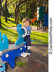 Toddler boy in seesaw in a sunny day - Toddler boy having...