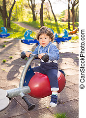 Little boy in seesaw - Little boy having fun on a seesaw in...