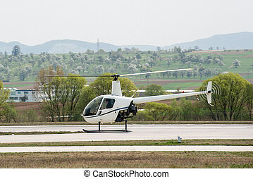Helicopter in flight along an airport in bright daylight