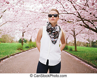 Fashionable young lady posing confidently at spring park -...