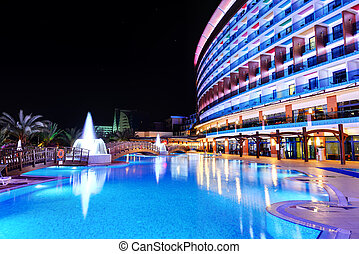 The swimming pool and building of luxury hotel in night...