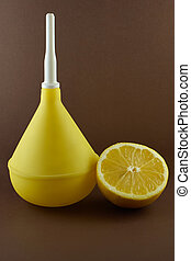 Medical enema with lemon on brown background - alternative...
