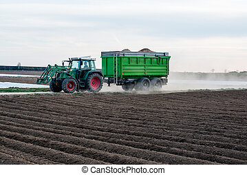 Modern tractor with trailer driving along agricultural field...
