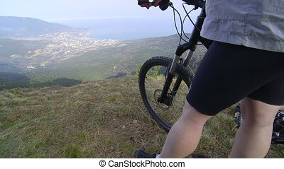 Cyclist with mountain bike stands on top of the mountain