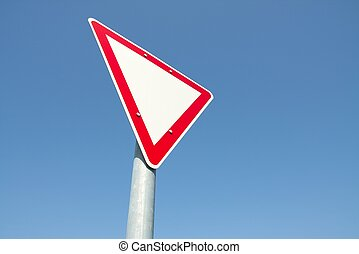 Yield traffic sign against clear blue sky