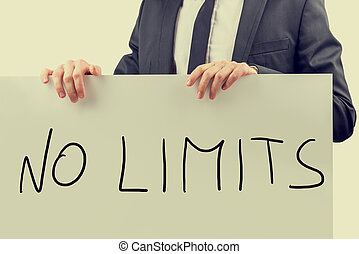 Businessman holding up a sign saying - No Limits -...