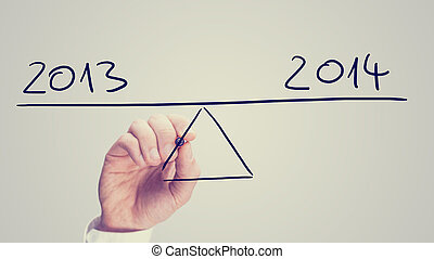 Man balancing 2013 and 2014 on a hand-drawn seesaw on a...