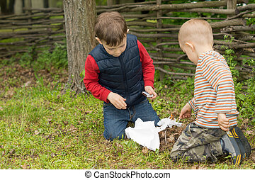 Two small boys trying to light a fire in a field squatting...