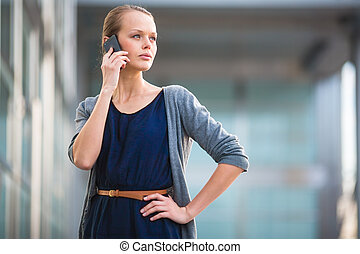 Portrait of a sleek young woman calling on a smartphone in...