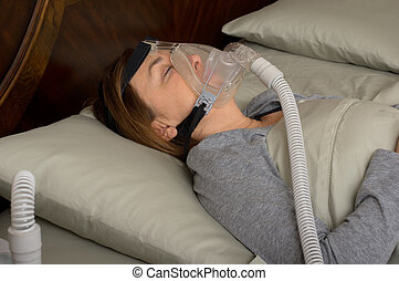 Sleep Apnea - Woman wearing CPAP machine for sleep apnea