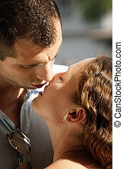 close up of sexy young couple aboout to kiss in the hot afternoon sunshine with their lips parted ready to meet