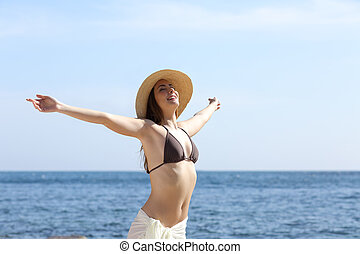 Happy woman breathing fresh air on the beach raising arms