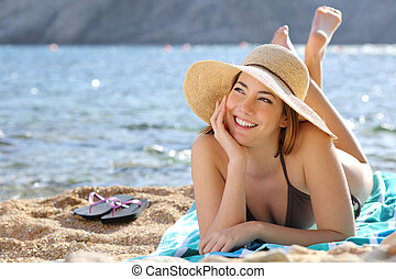 Happy woman thinking and looking at side lying on the beach...