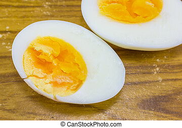 two halves of a boiled egg on wood background
