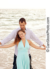 beautiful happy young adult couple at the ocean with arms outstr