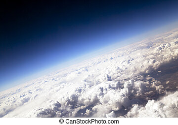 Blue sky and puffy clouds on height of 5000 m above Earth