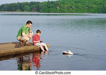 Father and son playing with a remote controlled boat