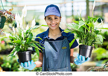 female gardener holding two potted flowers - pretty female...