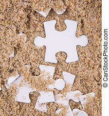 Jigsaw Puzzle Pieces Buried In Sand - Pieces of white jigsaw...