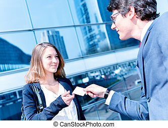 Junior executives dynamics exchange their business cards in...