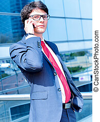 Junior executive dynamic phoning outside of his office