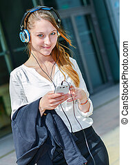 pretty worker listening to music in front her office