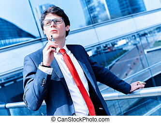 Cute young adult man inhaling from an electronic cigarette