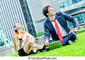 Successful Junior executives dynamics laying down on green...