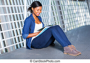 young african uni student reading a book